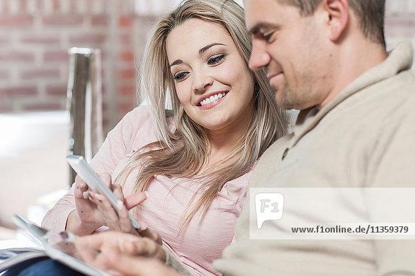 Paar zu Hause  auf dem Sofa entspannen  Smartphone anschauen