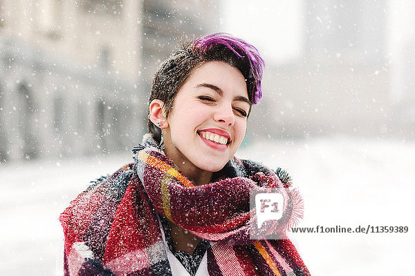 Portrait of young woman standing in front of the Christian Science Centre and Prudential building with snow  Boston  Massachusetts  USA