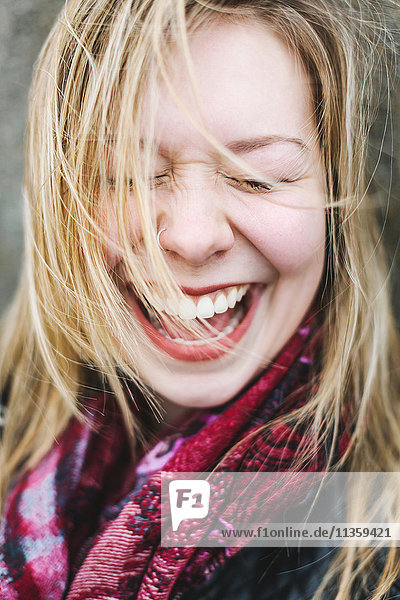 Portrait of woman with eyes closed laughing