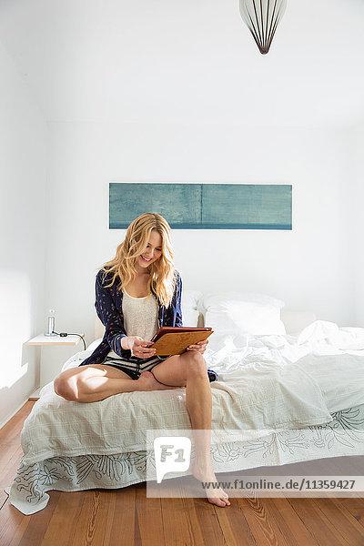 Frau sitzt auf Bett und benutzt digitales Tablett