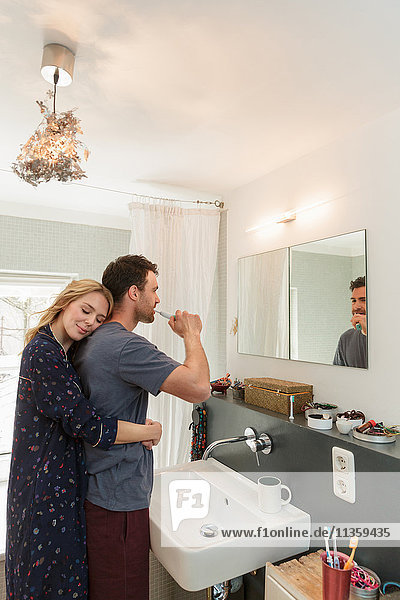 Paar im Badezimmer beim Zähneputzen