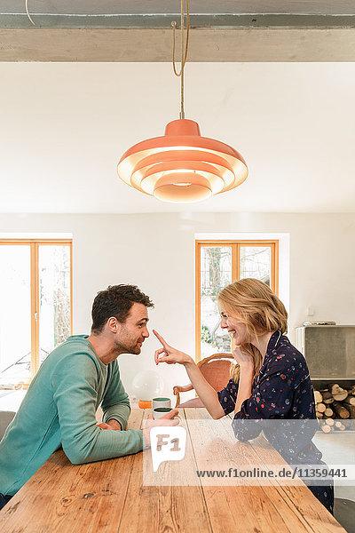 Paar von Angesicht zu Angesicht am Esstisch lächelnd