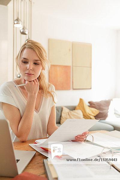 Frau mit Papierkram schaut auf Laptop
