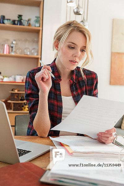 Frau mit Laptop sieht sich Papierkram an