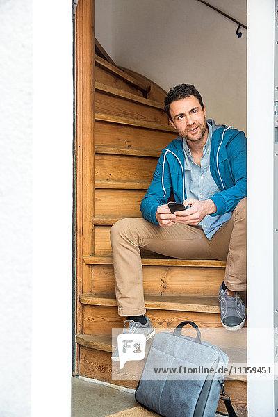 Mann mit Aktenkoffer sitzt auf Holztreppe und hält Telefon