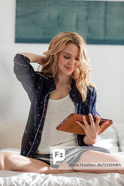 Frau sitzt mit digitalem Tablet auf dem Bett und lächelt