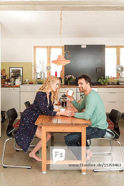 Ehepaar am Esstisch beim Kaffeetrinken