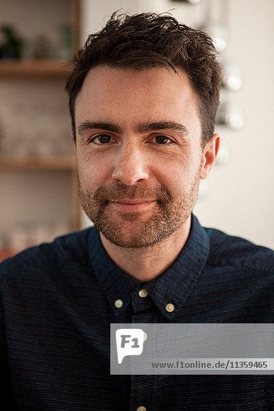 Porträt eines Mannes mit Stoppeln  der lächelnd in die Kamera blickt