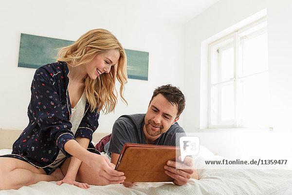 Paar im Bett mit digitalem Tablett lächelt