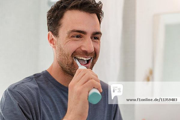 Mann putzt lächelnd die Zähne