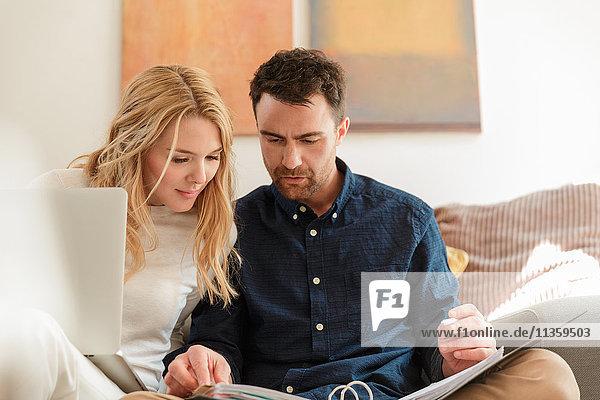 Paar mit Laptop beim Papierkram