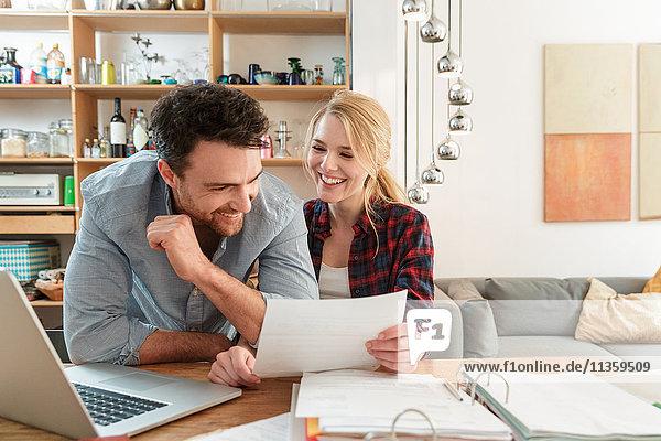 Paar mit Laptop schaut lächelnd auf Papierkram