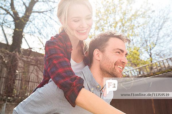 Mann gibt Frau Huckepack lächelnd