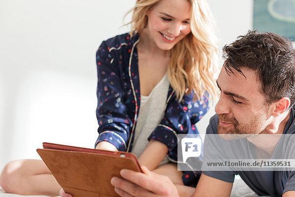 Ehepaar schaut lächelnd auf digitale Tablette