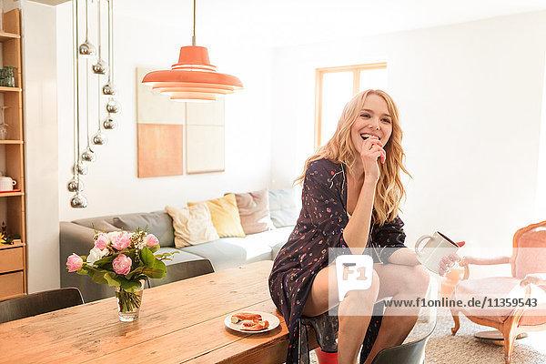Frau auf dem Esstisch hält Becher und schaut lächelnd in die Kamera