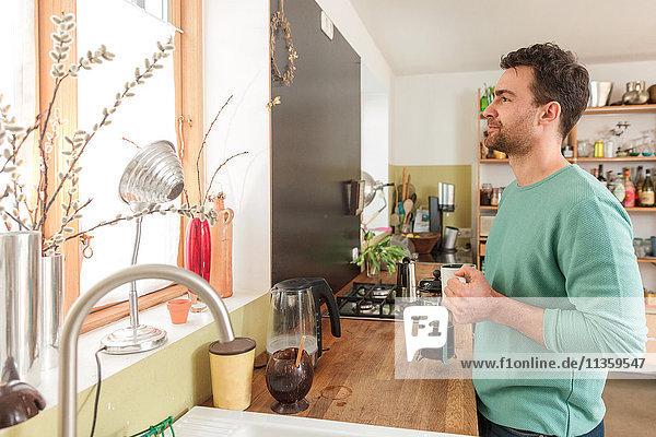 Mann in der Küche hält Kaffeetasse und schaut aus dem Fenster