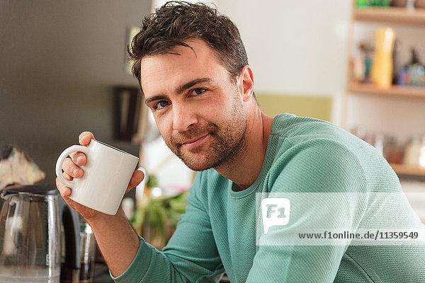 Porträt eines Mannes  der eine Kaffeetasse hält und lächelnd in die Kamera schaut