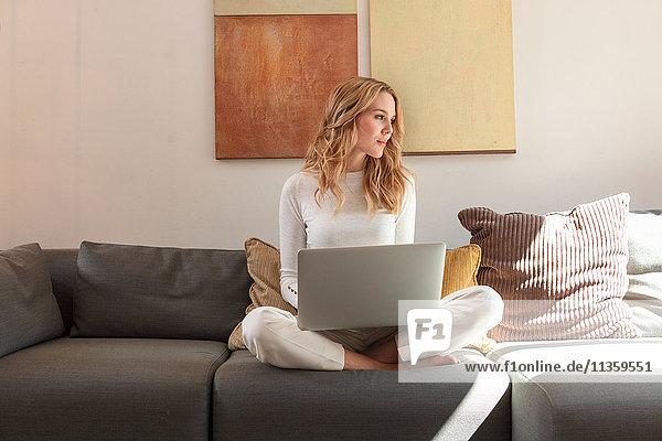 Frau auf dem Sofa mit Laptop und schaut weg