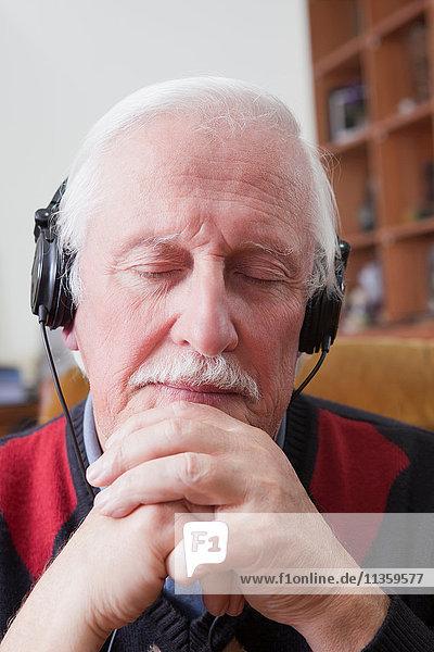 Senior Mann  der zu Hause Musik über Kopfhörer hört.