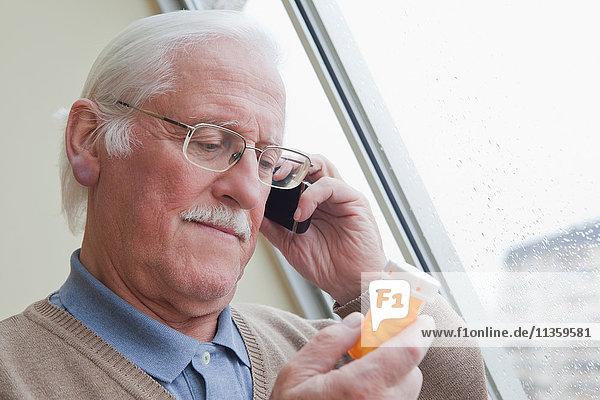 Senior Mann liest Etikett auf Pillenflasche zu Hause