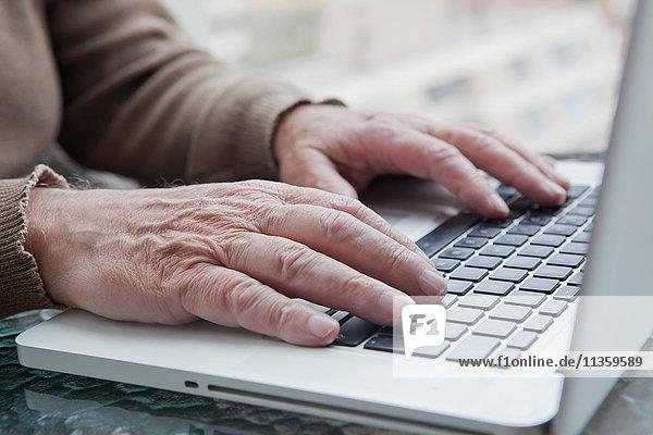 Älterer Mann benutzt Laptop zu Hause