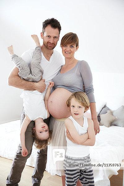 Schwangere Mutter mit Familie im Schlafzimmer
