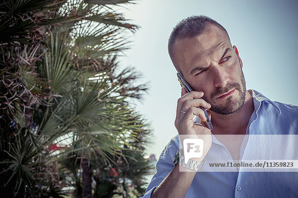 Serious businessman taking on smartphone against blue sky