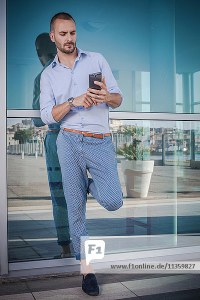 Businessman leaning against office exterior texting on smartphone  Cagliari  Sardinia  Italy