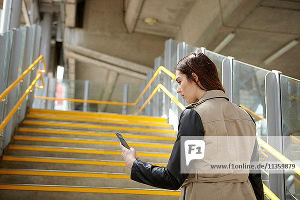 Rückansicht einer jungen Geschäftsfrau beim Lesen von Smartphone-Texten auf der Treppe  London  UK