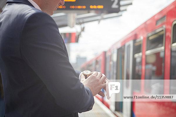 Ausschnitt eines Geschäftsmannes  der die Uhr auf dem Bahnsteig kontrolliert  London  UK