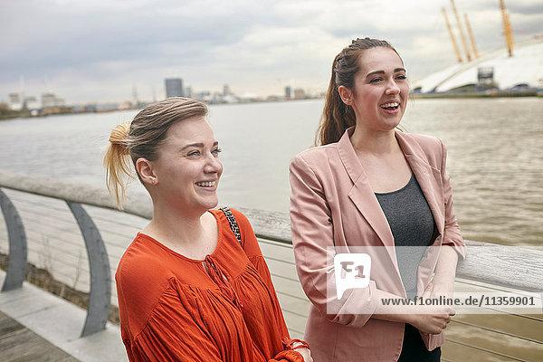Zwei junge Geschäftsfrauen im Gespräch am Wasser  London  UK