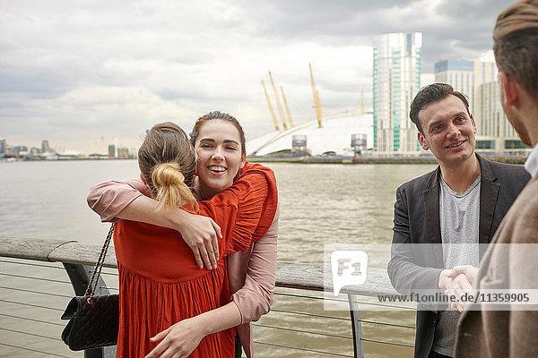 Geschäftsfrauen und Geschäftsleute grüßen am Wasser  London  UK