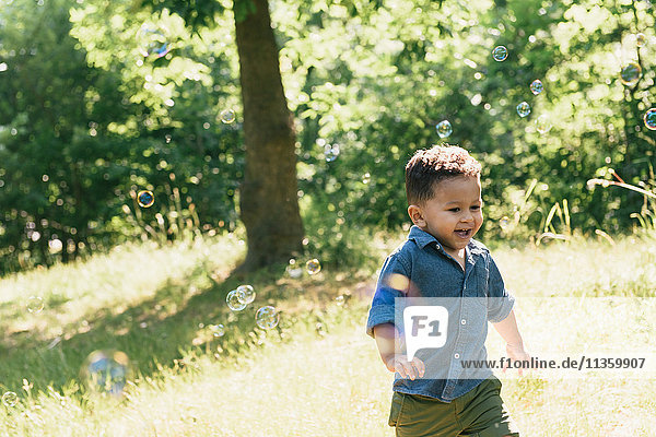 Male toddler running among floating bubbles in Pelham Bay Park  Bronx  New York  USA