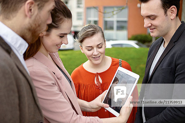 Geschäftsfrauen und Geschäftsleute auf der Suche nach digitalen Tabletts  London  UK