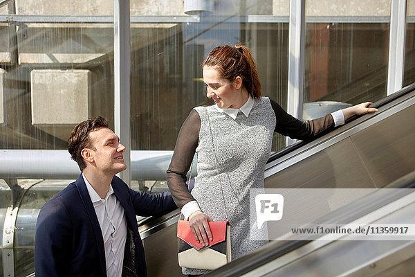 Geschäftsfrau und Geschäftsmann im Gespräch auf der Rolltreppe  London  UK