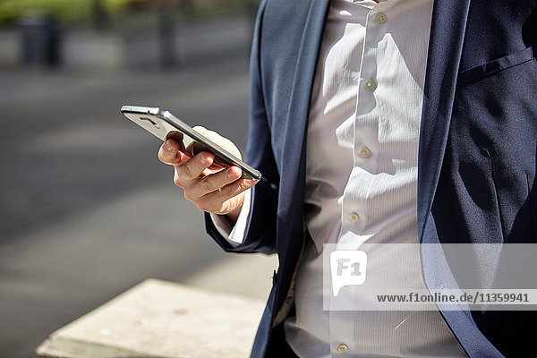 Mid Abschnitt der Geschäftsmann SMS auf Smartphone in der Stadt