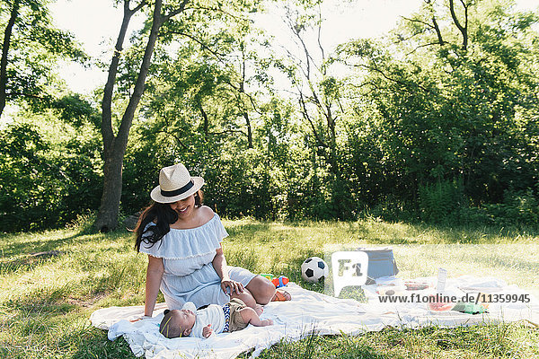 Mid adult woman and baby son on picnic blanket in Pelham Bay Park  Bronx  New York  USA