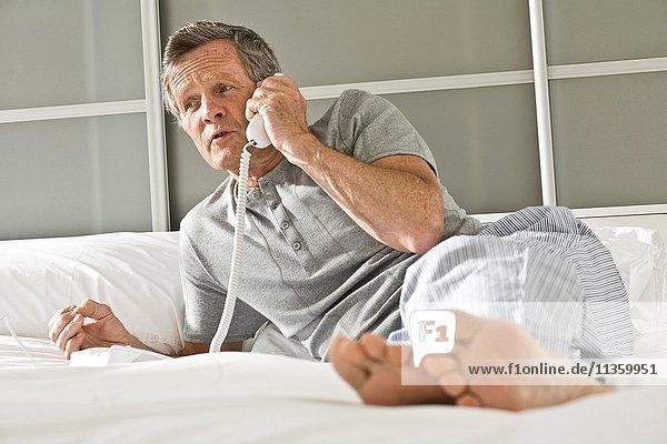 Senior auf dem Bett liegend  am Festnetztelefon sprechend