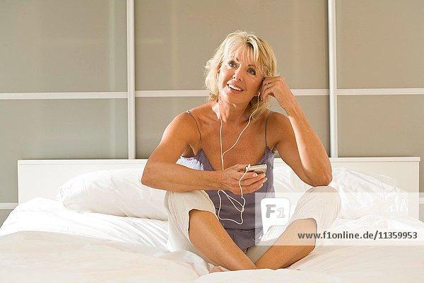 Reife Frau sitzt im Bett und hört Kopfhörer.