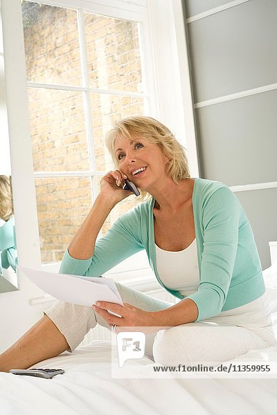 Mature woman sitting up on bed using mobile phone to pay bills