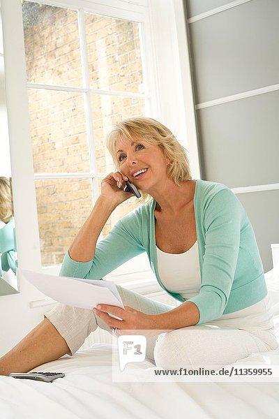 Reife Frau auf dem Bett sitzend mit dem Handy Rechnungen bezahlen