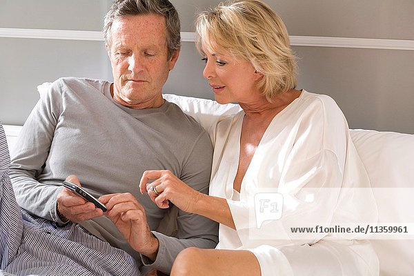 Couple sitting up in bed reading mobile phone texts