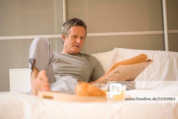 Älterer Mann sitzt im Bett und liest Zeitung.