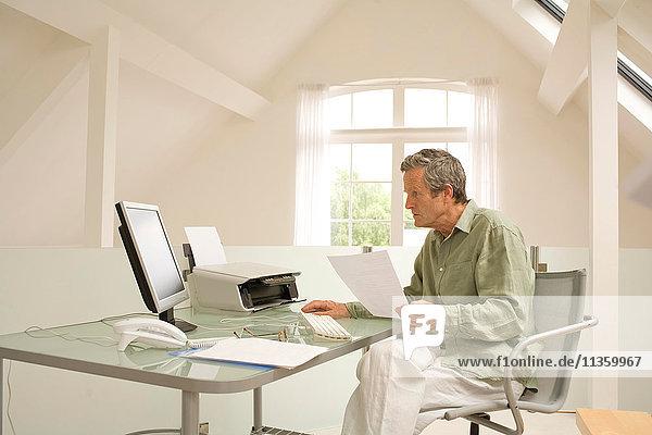 Senior Mann  der den Computer benutzt und Papierkram zu Hause erledigt