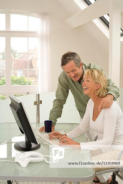 Paar mit Computer und Lachen zu Hause am Schreibtisch
