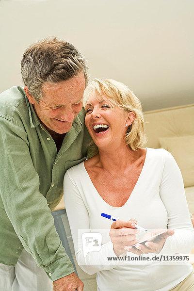 Ein Paar macht sich Notizen und lacht zu Hause.
