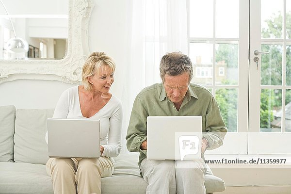 Paar auf Sofa mit Laptops