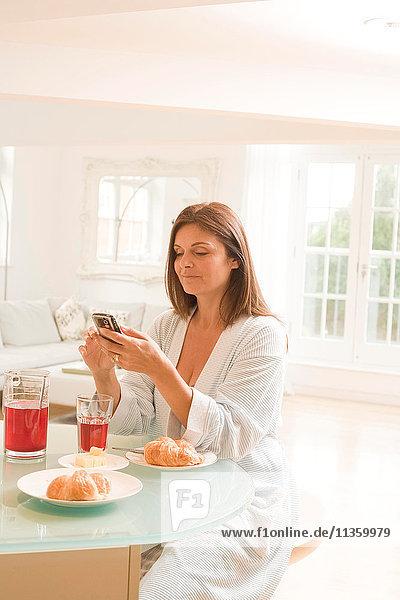 Reife Frau am Frühstückstisch beim Lesen von Handytexten