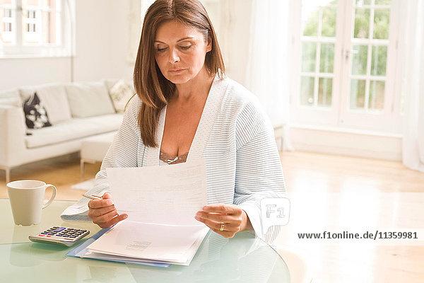 Reife Frau am Tisch beim Lesen von Rechnungen
