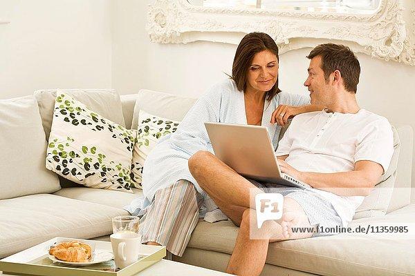 Reife Paare auf dem Sofa beim Durchstöbern des Laptops und Frühstücken